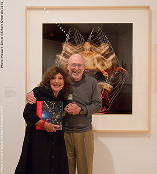 gail buckland holding the who shot sports book standing with howard schatz in front of his photograph